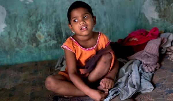 Ein traurig blickendes indisches Mädchen im Schneidersitz