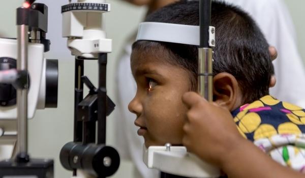 Indisches kleines Kind schaut durch ein Gerät zur Augenuntersuchung