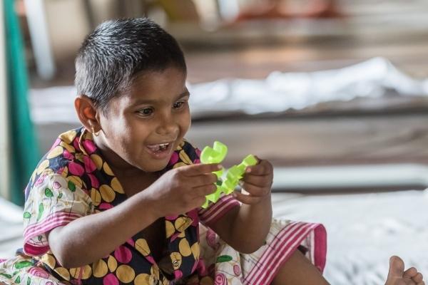 Kleines indisches Mädchen schaut ein buntes Plastikspielzeug an