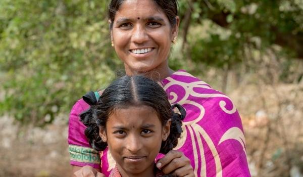 Eine Frau in pinkfarbenem Sari und ein Mädchen mit Zöfen