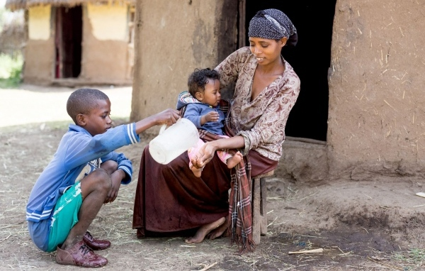 Ein Junge gießt Wasser in die Hand einer Frau, auf deren Schoß ein Baby sitzt