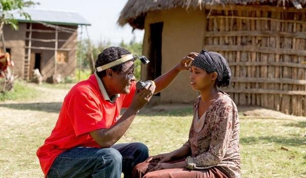 Ein Mann untersucht im Freien die Augen einer Frau