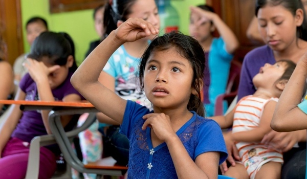 Ein Mädchen macht Zeichen mit den Händen.