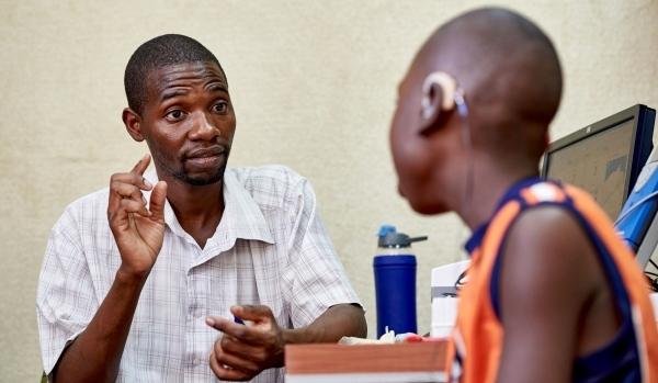 Ein Mann spricht mit einem Kind, das ein Hörgerät trägt.