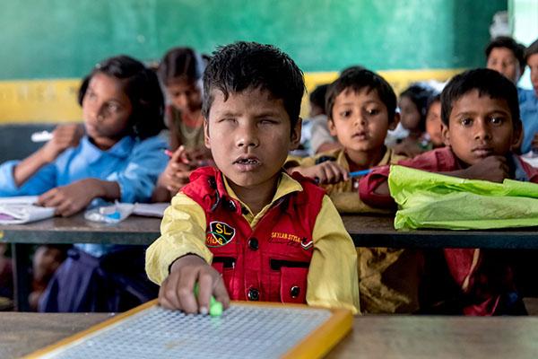 Ein Junge benutzt einen Griffel beim Schreiben von Blindenschrift