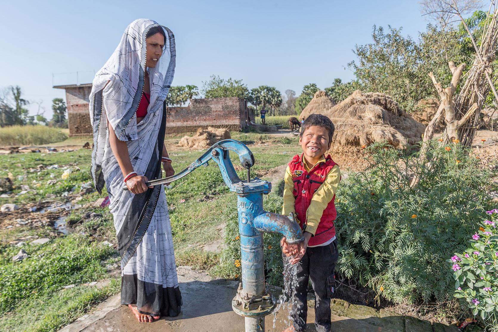 Ein kleiner Junge wäscht sich an einer Pumpe die Hände. Seine Mutter steht daneben und betätigt die Pumpe.