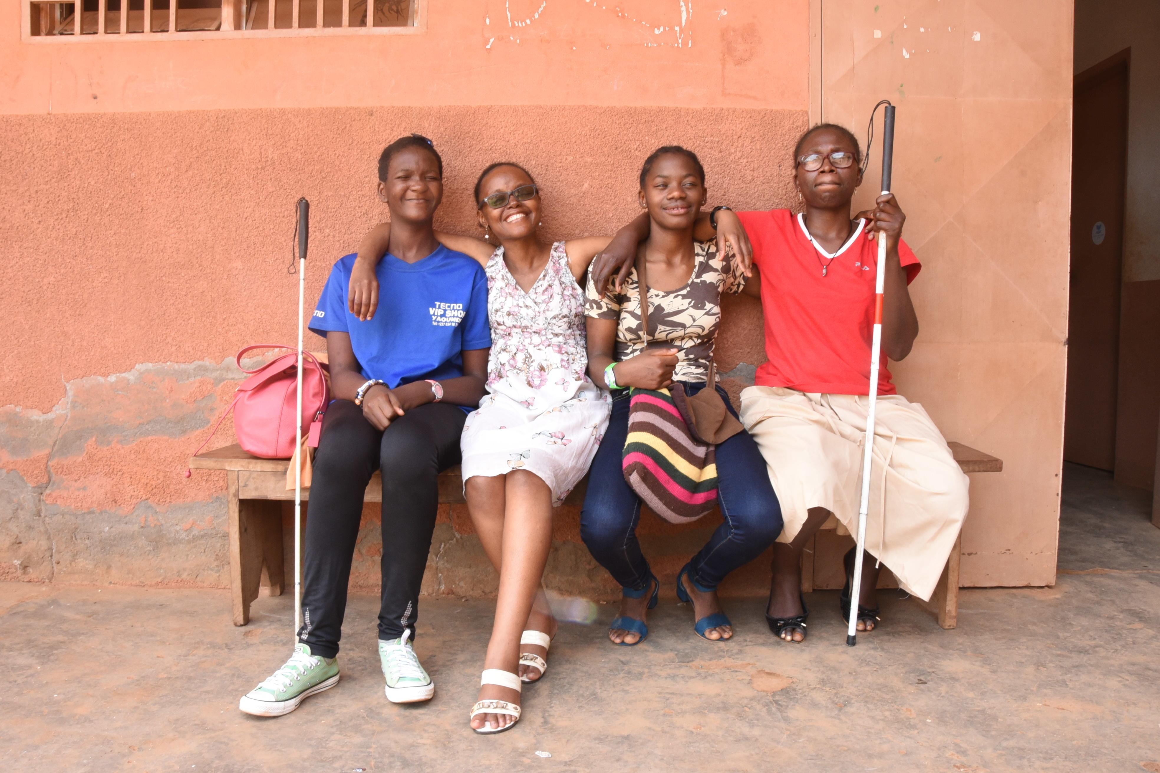 Vier junge Frauen sitzen lächelnd auf einer Bank. Zwei von ihnen haben Blindenstöcke.
