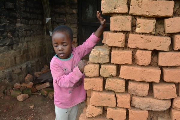 Kleiner Junge tastet sich an einer Steinmauer entlang