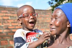 Lachender Junge mit Brille auf dem Arm einer Frau