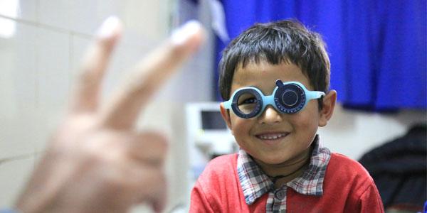Lächelnder nepalischer Junge mit Sehtest-Brille