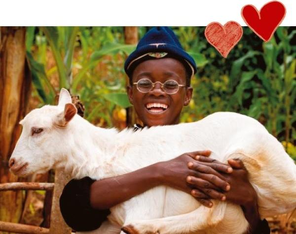 Ein lachender Junge mit Brille hält eine junge Ziege auf dem Arm.