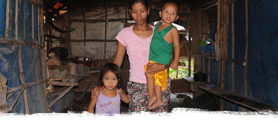 Frau mit zwei kleinen Kindern in einer einfachen Hütte aus Zweigen und Planen