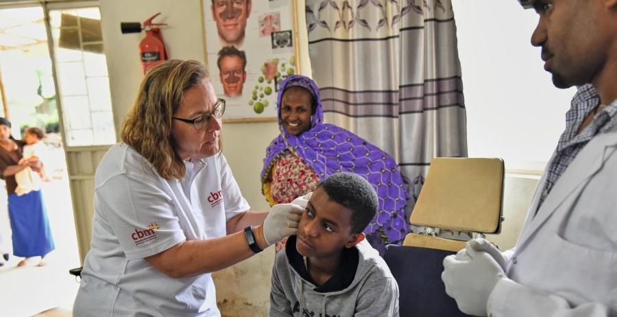 Eine Frau untersucht das Ohr eines Jungen