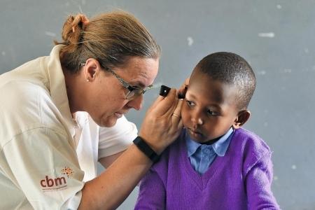 Eine Frau untersucht das Ohr eines Jungen.