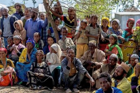 Bunt gekleidete afrikanische Menschen stehen oder sitzen unter einem Baum