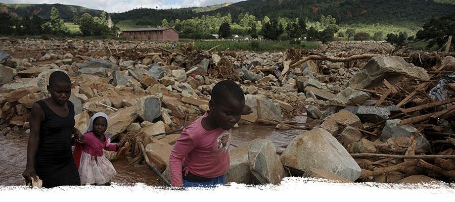 Drei Kinder laufen durch ein Trümmerfeld, das Zyklon Idai hinterlassen hat.