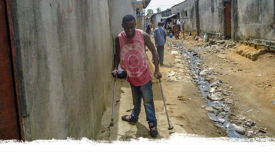 Ein junger Mann aus der Elfenbeinküste humpelt mit Krücken eine schmutzige Straße entlang.