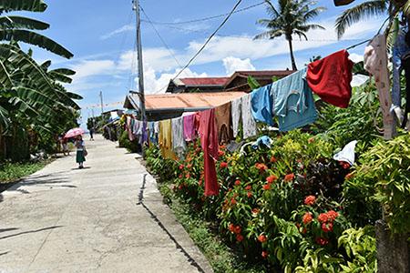 Eine asphaltierte Straße in einem philippinischen Dorf, gesäumt von Kleidungsstücken auf einer Wäscheleine.