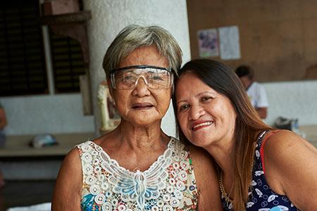 Mutter uns Tochter sitzen lächelnd nebeneinander. Die Mutter wurde am Tag vorher am Grauen Star operiert und trägt nun eine Schutzbrille.