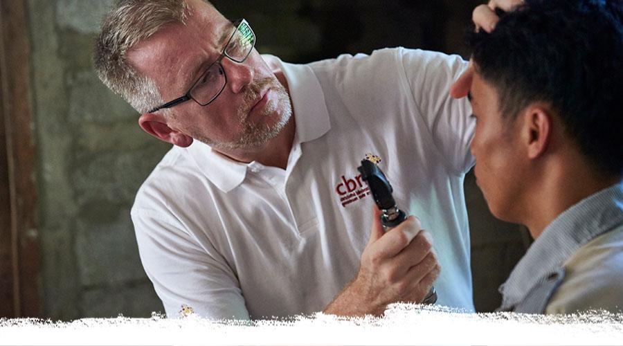 Augenarzt Dr. Manfred Mörchen untersucht einen Patieten in dessen Haus.