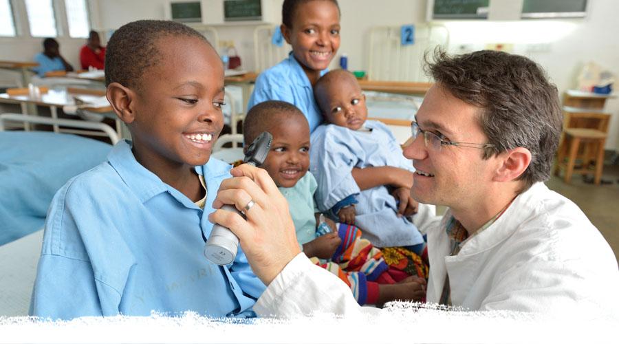 Augenarzt Dr. Heiko Philippin untersucht ein kleines Mädchen an den Augen mit einer Lampe. Im Hintergrund warten ihre drei Geschwister. Alle lächeln.