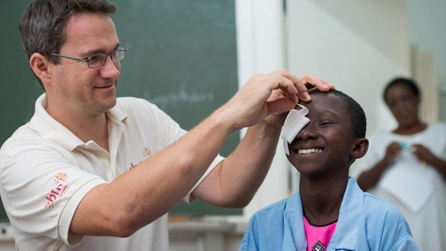 Augenarzt Dr. Heiko Philippin nimmt einem Jungen den Augenverband verband ab. Beide lächeln.