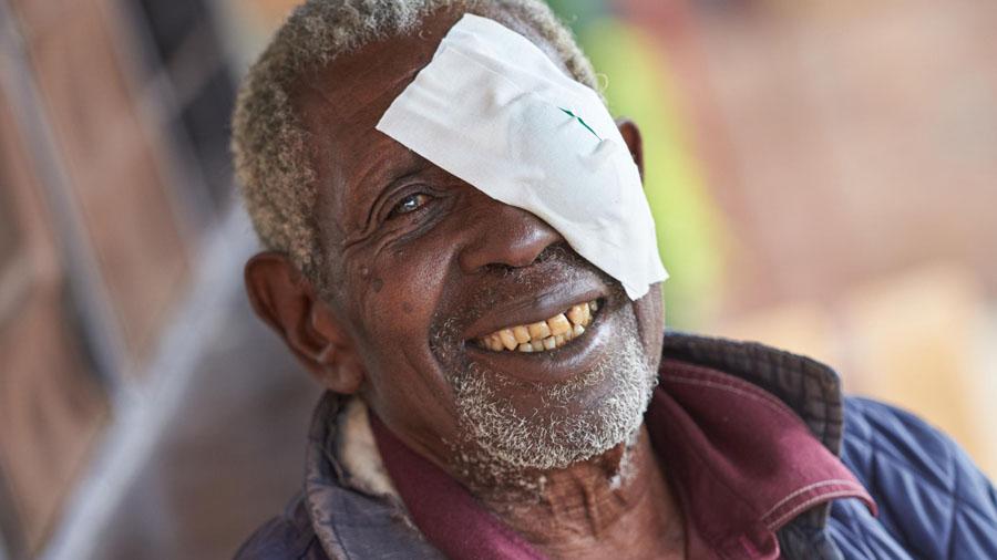 Älterer lächelnder Mann aus Afrika mit Augenverband.
