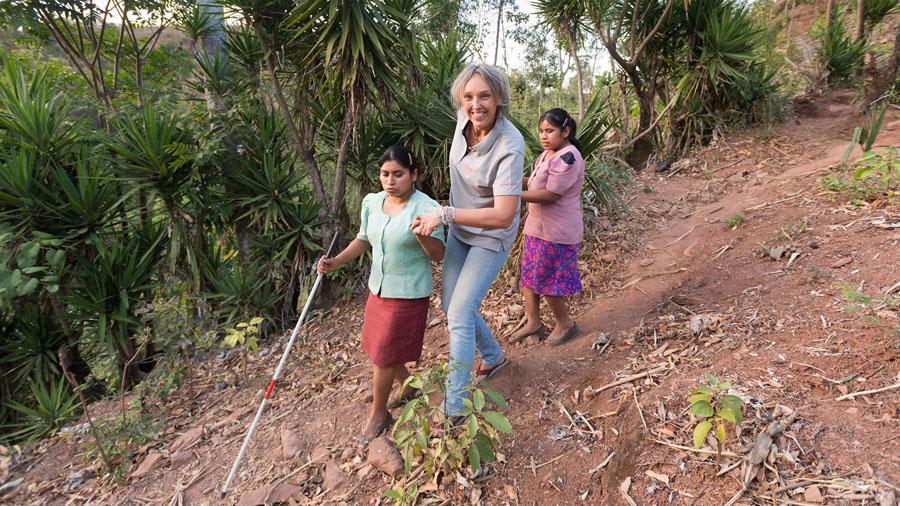 Drei Frauen laufen einen Berghang hinunter. Zwei Frauen sind blind, eine mit Langstock.