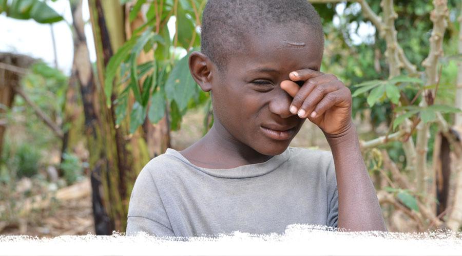 Ein blinzelnder Junge aus Uganda hält seine Hand vors linke Auge.