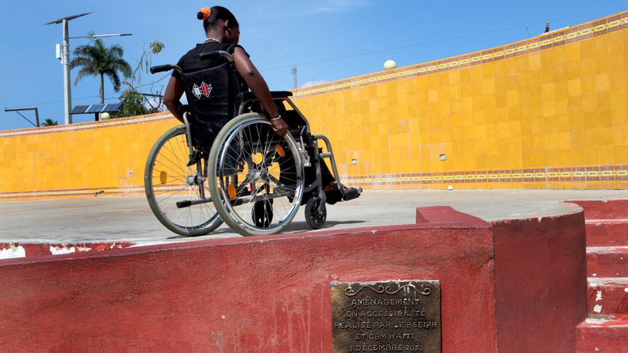 Eine Frau im Rollstuhl fährt eine Rampe hinauf.