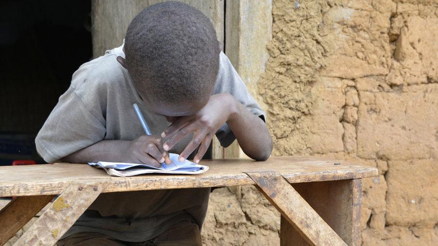 Ein fast blinder Junge aus Uganda ist über ein Schulheft gebeugt und versucht zu schreiben.