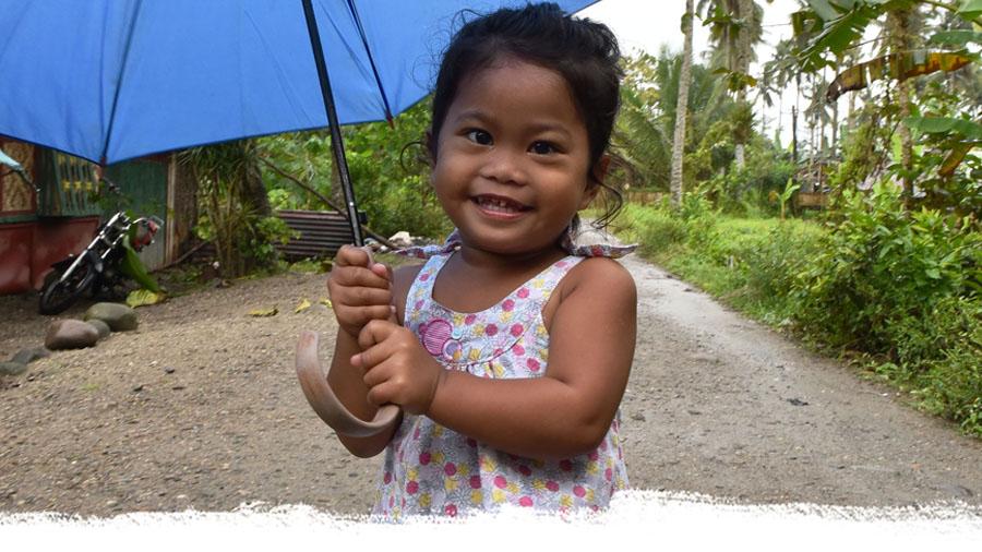 Lächelndes philippinisches Mädchen mit Regenschirm