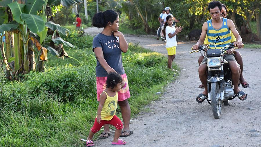 Philipppinisches Mädchen rennt beinhahe gegen ein fahrendes Motorrad