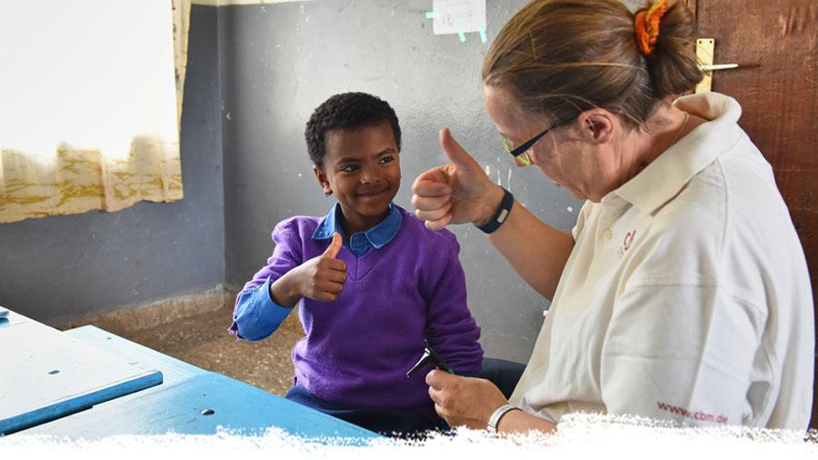 Ärztin und kleines Mädchen zeigen Daumen hoch