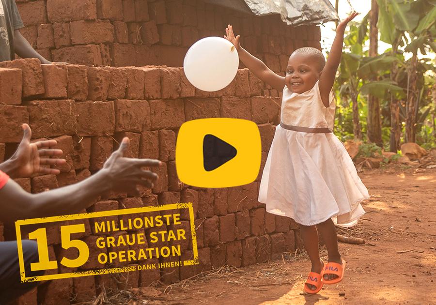 Video-Play-Button: Ein kleines afrikanisches Mädchen wirft einen Luftballon und hüpft dabei hoch. Stempel mit 15 MILLIONSTE GRAUE STAR OPERATION.