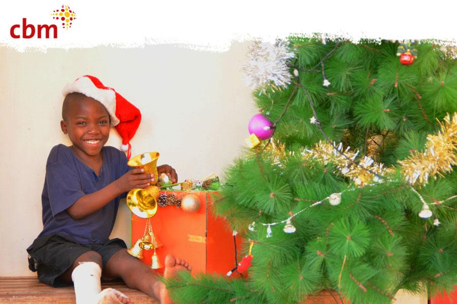 Afrikanischer Junge mit Gipsverband am Bein sitzt lächelnd mit Geschenken unter dem Weihnachtsbaum